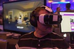 Mannen försöker hörlurar med mikrofon för det virtuell verklighetSamsung kugghjulet VR Royaltyfri Bild