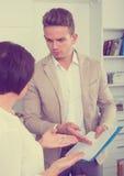 Mannen försöker kvinnan för att underteckna dokument Royaltyfria Foton