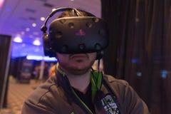 Mannen försöker virtuell verklighethörlurar med mikrofon Arkivfoto
