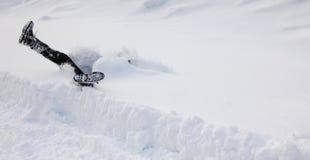 Mannen faller huvudstupa in i djup snö Begrepp av winterly hala villkor royaltyfri fotografi