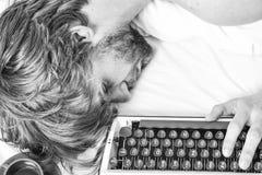 Mannen faller sovande Författare använd gammalmodig skrivmaskin Författaren rufsade till hår faller sovande, medan skriv boken Ar arkivfoton