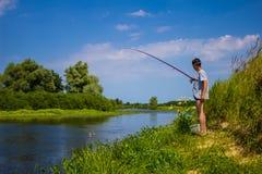 Mannen fiskar på banken av floden med en metspö i sommar arkivbild