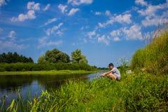 Mannen fiskar på banken av floden med en metspö i sommar royaltyfri fotografi