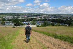 Mannen fotvandrar till den Glastonbury festivalen i Somerset, England Royaltyfri Foto