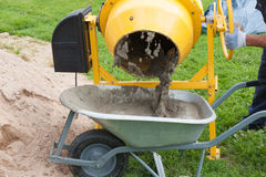 Mannen fyller den trädgårds- vagnen med cement Royaltyfria Bilder