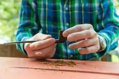 Mannen fyller hans rör med tobak royaltyfria bilder