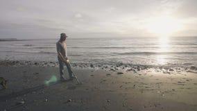 Mannen går med hunden på strandinnehavavkännaren som finner metall i sanden på kustlinjen på soluppgång arkivfilmer