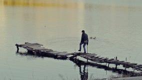 Mannen går på en skröplig bro stock video