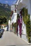 Mannen går på en trottoar i en gataplats från Positano, den Amalfi kusten, Italien royaltyfri bild