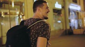 Mannen går på gatan av vänden för nattstadscloseupen för att se kameran och leenden lager videofilmer