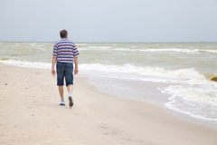 Mannen går på havsstranden Royaltyfria Foton
