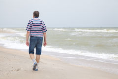 Mannen går på havsstranden Royaltyfri Fotografi