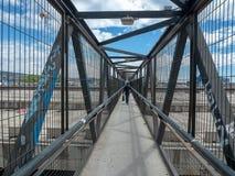 Mannen går på metallbron arkivfoto
