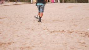 Mannen går på stranden med en metalldetektor Han försöker att finna juvlar och mynt Solig strandkust lager videofilmer