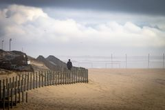 Mannen går på strandpromenad på stranden arkivbild
