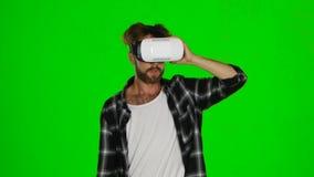Mannen går runt om rummet i en maskering av virtuell verklighet grön skärm stock video