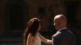 Mannen går till den rika brunettdamen som ut når henne händer till honom arkivfilmer