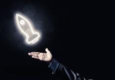 Mannen gömma i handflatan framlägga raketrengöringsduksymbolen som teknologibegrepp Royaltyfria Bilder
