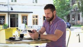 Mannen gör anmärkningar från smartphonen till anteckningsboken i kafét, glidareskottet som lämnas lager videofilmer