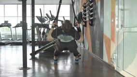 Mannen gör crossfithandtag ups med trxkonditionremmar i idrottshall arkivfilmer