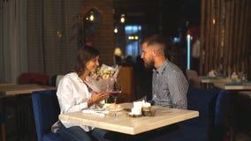 Mannen gör en överraskning med blommor för en kvinna i restaurangen stock video