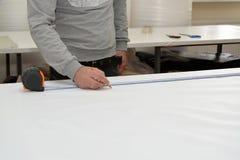 Mannen g?r en markering p? en PVC-film Shoppa p? produktion av elasticitetstak arkivbild