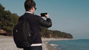 Mannen gör en serie av foto på bakgrunden av havet, honom kan vara en turist arkivfilmer