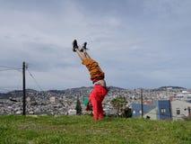 Mannen gör handstans överst på kullen framme av byggnader royaltyfri foto