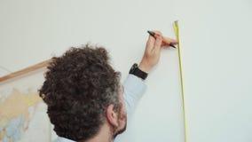 Mannen gör mätningar med linjalen och blyertspennan på väggen stock video