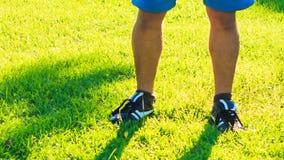 Mannen gör morgonövningskrökningar till fot på gräsmatta för grönt gräs lager videofilmer