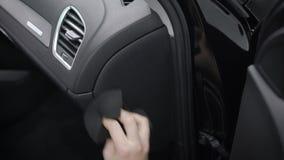 Mannen gör ren kontrollbordet inom en bil och att gnida den vid den mjuka torkduken och att ta bort damm och smuts, närbilden lager videofilmer