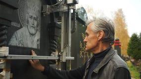 Mannen gör ren stenen och kontrollerar gravyren arkivfilmer