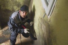 Mannen gör ren väggarna av stark smuts med en borste och en trasa Arbetaren tvättar korridorväggarna manuellt Form och arkivfoto