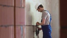 Mannen gör spåren i väggen genom att använda väggeftersläckare lager videofilmer