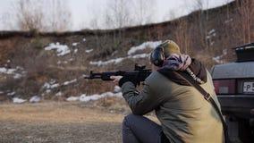Mannen gör två skott från ett anfallgevär från en sittande position Slapp fokus stock video