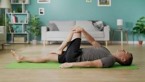 Mannen g?r yoga hemma i morgonen i hans vardagsrum arkivfilmer