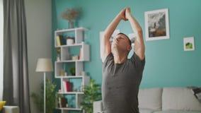 Mannen g?r yoga hemma i morgonen i hans vardagsrum stock video