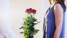 Mannen ger en bukett av röda rosor till en kvinna Royaltyfri Bild