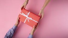 Mannen ger en flicka en gåva från handen för att räcka, asken som slås in i dekorativt papper på bakgrund, begreppet av ferier, f arkivfoto