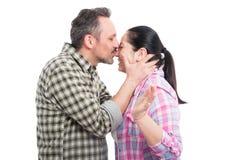 Mannen ger hans flickvän en känslig kyss Arkivfoto