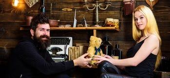 Mannen ger sig till damnallebjörnen som gåvan på årsdag Par som är förälskade på att le framsidor, tycker om ferie Par spenderar  Royaltyfria Bilder