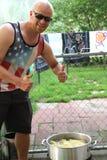 Mannen ger upp tummar för havre på majskolven på feriepicknicken Arkivbild