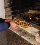 Mannen grillar kött med griskött på gallret royaltyfri fotografi