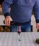 Mannen häller ett rött vin i ett exponeringsglas mot den brinnande flamman av spisen arkivbilder