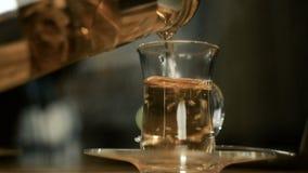 Mannen häller grönt te in i en glass kopp från bryggaren Närbild arkivfilmer