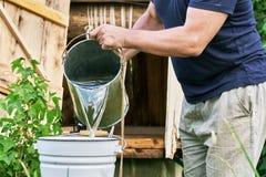 Mannen häller in i en hink av vatten som tas precis från brunnen arkivfoto