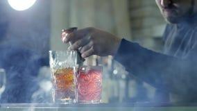 Mannen häller konjak från grej in i drinken med is i exponeringsglas på tabellen i ljus ogenomskinlighet på unfocused bakgrund stock video