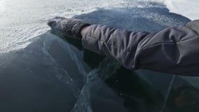 Mannen häller snö på isen långsam rörelse Partiklar av snö sprider beautifully på isen Männen i tumvantena lager videofilmer