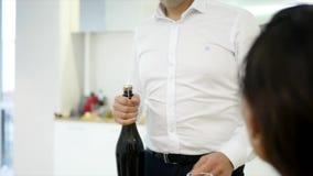 Mannen häller två exponeringsglas av champagne för att fira flyttning in i nytt hem med flickvännen stock video