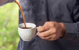 Mannen häller varma kaffe från kaffekrukan in i koppen Arkivfoto